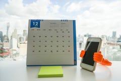 Calendrier de décembre avec les notes et le smartphone collants Photo stock