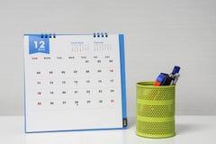 Calendrier de décembre sur le bureau avec la boîte stationnaire Images stock