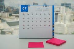 Calendrier de juillet avec la moquerie de rose vers le haut du post-it pour laisser le message pour rappeler des participants et  Photographie stock libre de droits