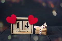 Calendrier en bois avec la date du coeur du 14 février et de papier et du cadeau Sur un fond en bois foncé avec l'espace de copie Photographie stock