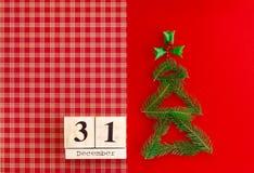 Calendrier en bois avec la date du 31 décembre sur le fond rouge à carreaux Nouvelle année et concept de Noël, décorations photographie stock libre de droits