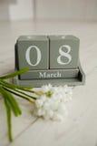 Calendrier en bois avec le 8 mars et floowers sur le fond blanc Images libres de droits