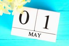 Calendrier en bois blanc avec le texte : 1er mai Fleurs blanches des jonquilles sur une table en bois bleue Fête du travail et re Images libres de droits