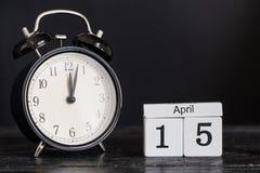 Calendrier en bois de forme de cube pour le 15 avril avec l'horloge noire Photos stock