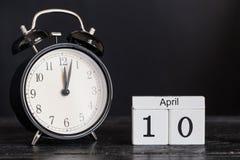Calendrier en bois de forme de cube pour le 10 avril avec l'horloge noire Photo libre de droits