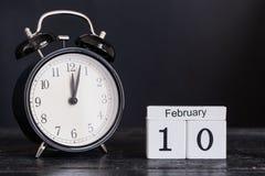 Calendrier en bois de forme de cube pour le 10 février avec l'horloge noire Photographie stock libre de droits