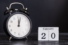 Calendrier en bois de forme de cube pour le 20 février avec l'horloge noire Photos libres de droits