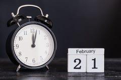 Calendrier en bois de forme de cube pour le 21 février avec l'horloge noire Images libres de droits