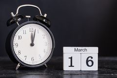 Calendrier en bois de forme de cube pour le 16 mars avec l'horloge noire Photo stock