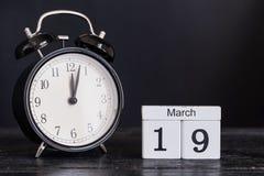Calendrier en bois de forme de cube pour le 19 mars avec l'horloge noire Photographie stock