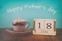 Calendrier en bois de vintage le 18ème juin à côté de la tasse du café et de la moustache Image libre de droits