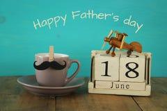 Calendrier en bois de vintage le 18ème juin à côté de la tasse du café et de la moustache Photo libre de droits