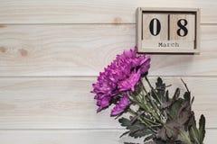 Calendrier en bois du 8 mars, à côté des fleurs pourpres sur la table en bois Image libre de droits