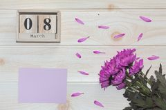 Calendrier en bois du 8 mars, à côté des fleurs pourpres sur la table en bois Photo libre de droits