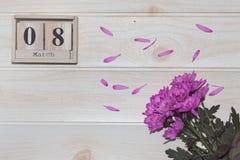 Calendrier en bois du 8 mars, à côté des fleurs pourpres sur la table en bois Images stock