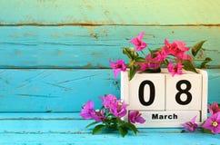Calendrier en bois du 8 mars, à côté des fleurs pourpres sur la vieille table rustique bleue Foyer sélectif Photo stock