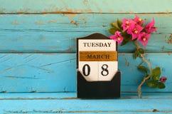 Calendrier en bois du 8 mars, à côté des fleurs pourpres sur la vieille table rustique bleue Foyer sélectif Photographie stock