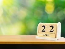 Calendrier en bois sur l'exposition en bois de bureau la date du 22 avril Photographie stock libre de droits