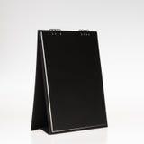 Calendrier noir de table de spirale de papier de couverture sur le backg blanc Images libres de droits