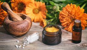 Natural medicine. Essential oil, ointment a mortar and white pills on a wooden table, fresh blooming calendula background, stock image