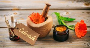 Calendula aromatherapy. Essential oil and herbal ointment, text calendula on a tag. Wooden table background. Calendula or pot marigold aromatherapy. Essential Royalty Free Stock Images