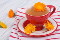 Calendula flower tea on striped tablecloth Royalty Free Stock Image