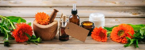 Calendula aromatherapy. Essential oil and cosmetics, blank tag, banner. Wooden table background. Calendula or pot marigold aromatherapy. Essential oil and Stock Photos