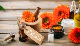 Calendula products. Essential oil, globules and cosmetics, tag with text calendula. Wooden table background. Calendula or pot marigold products. Essential oil Royalty Free Stock Images