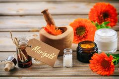 Pot marigold products. Essential oil, globules and cosmetics, tag with text marigold. Wooden table background. Calendula or pot marigold products. Essential oil Royalty Free Stock Images