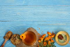 Calendula tea with fresh and dried flowers on blue wooden background with copy space for your text. Top view.  Stock Photography