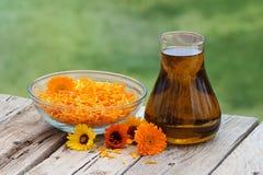 Calendulabloemen en olie Stock Foto