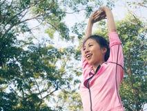 Calentamiento asiático de la mujer joven el cuerpo que estira antes de ejercicio y de yoga de la mañana en el parque bajo mañana  imagen de archivo