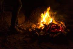 Calentamiento cerca de una hoguera en la noche romántica oscura Imagen de archivo libre de regalías