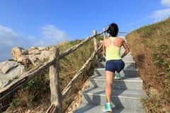 Calentamiento del corredor del rastro de la mujer en las escaleras de la montaña Fotografía de archivo