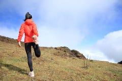 Calentamiento del corredor del rastro de la mujer en pico de montaña foto de archivo libre de regalías