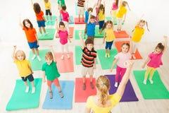 Calentamiento durante la lección gimnástica para los niños en gimnasio fotos de archivo libres de regalías
