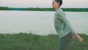 Calentamiento hermoso de la mujer para hacer práctica de la yoga de la mañana Forma de vida sana almacen de video