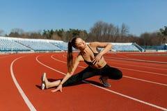 Calentamiento joven del corredor de la mujer de la aptitud antes de correr en pista fotografía de archivo libre de regalías