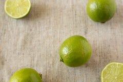 Cales verdes enteras y cortadas de la fruta cítrica en el paño, opinión de ángulo bajo imagen de archivo libre de regalías