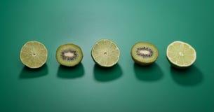 Cales y kiwis verdes en un fondo verde fotografía de archivo