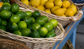 Cales y limones en cestas Fotos de archivo