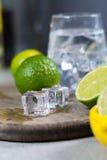 cales y vidrio con los cubos de hielo Imagen de archivo