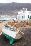Caleta de Famara, Лансароте, Palmas/SPAIN - 2-ое февраля 2018: Рыбацкая лодка на берег и опорожняет внешний ресторан, с морем в t стоковое фото rf