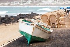 Caleta de Famara, Lanzarote, Palmas/SPAIN - 2 Φεβρουαρίου 2018: Αλιευτικό σκάφος στην ξηρά και κενό υπαίθριο εστιατόριο, με τη θά στοκ εικόνες