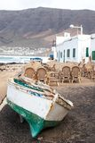 Caleta de Famara, Lanzarote, Palmas/SPAIN - February 2, 2018: Fishing boat ashore and empty outdoor restaurant, with the sea in th Royalty Free Stock Photo