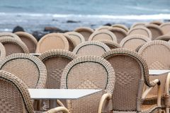 Caleta de Famara/SPAIN - February 2, 2018: Chairs and tables of an empty outdoor restaurant with the sea in the background Royalty Free Stock Image