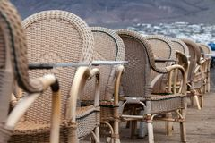Caleta de Famara/SPAIN - February 2, 2018: Chairs and tables of an empty outdoor restaurant with the sea in the background Stock Image