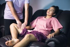Calf and leg Thai massage in spa. Calf and leg massage to beautiful Asian tan woman on sofa. Traditional Thai spa treatment. Health care and Relax to heal pain Stock Photo