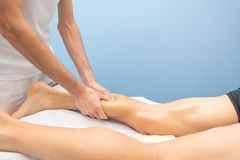 Calf massage to an athlete by a professional physiotherapist royalty free stock photo