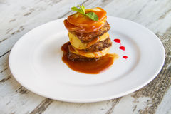 Calf's liver with apples Laid layers with sauce on a white plate Stock Photography